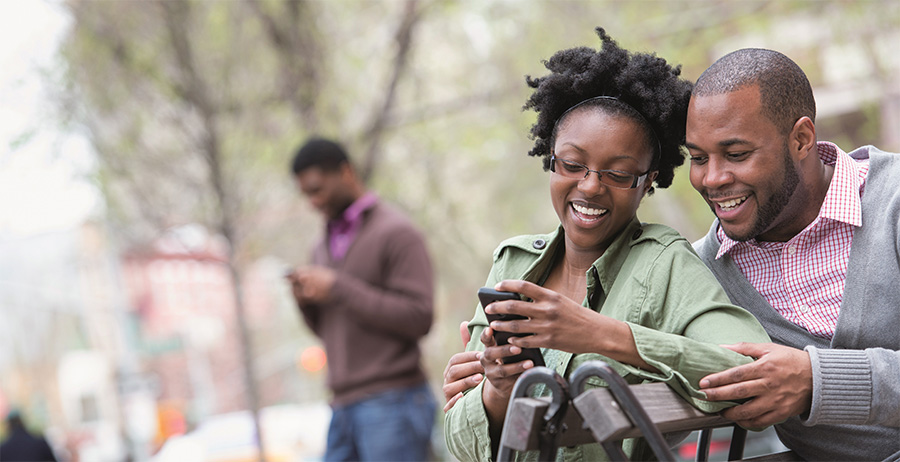 smiling couple sitting on bench looking at cell phone
