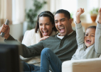 Wife, husband, and young child siting on the couch, cheering, while watching TV