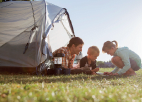Father with young son and daughter sitting outside of tent looking at tablet